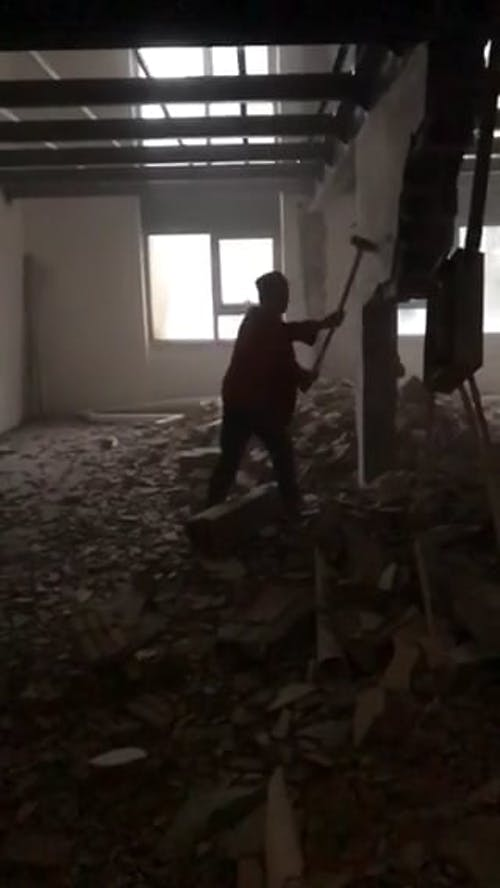Man Demolishing a Wall of a Building