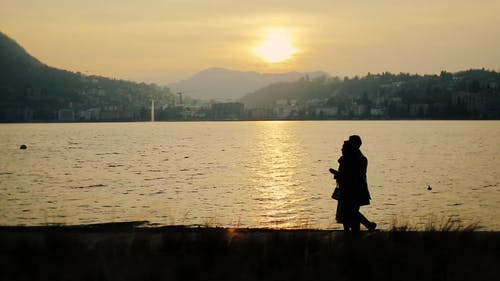 Silhouette Of Two Persons Walking Along The River