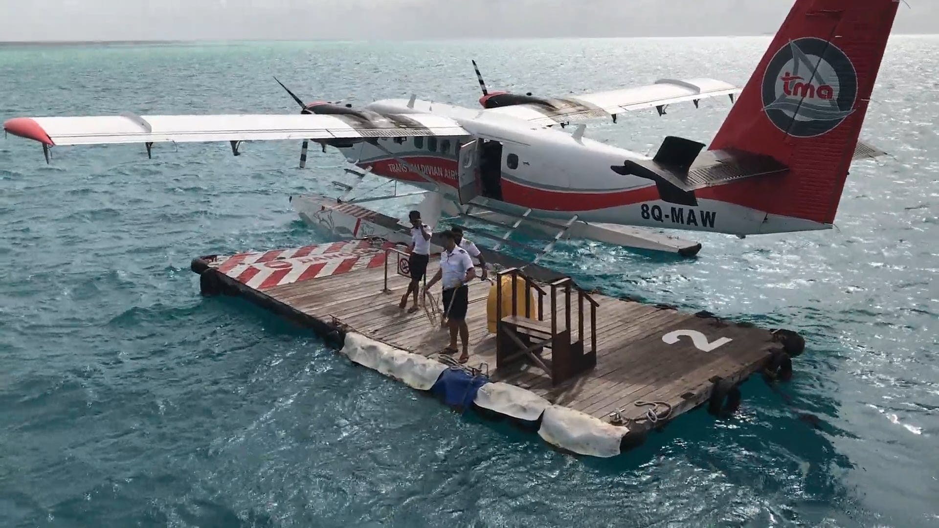 Airplane On Water With People Helping Others