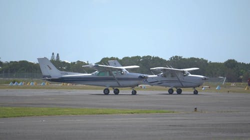 Two Private Airplanes Waiting On The Runway