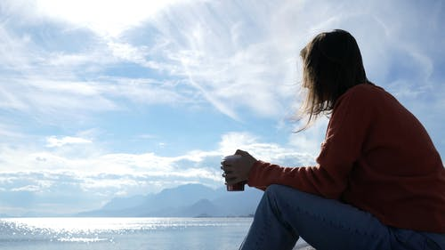 Person Drinking Coffee While Viewing The Sea