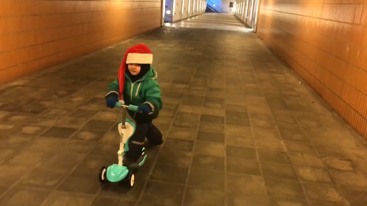Child Having Fun Riding A Scooter