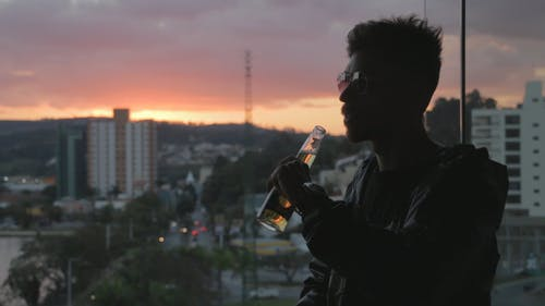 Man Drinking With Sunset Background