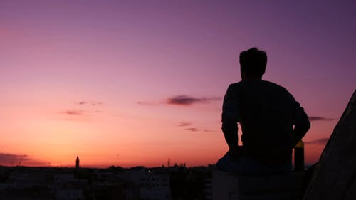 Silhouette of a Man Sitting on the Roof