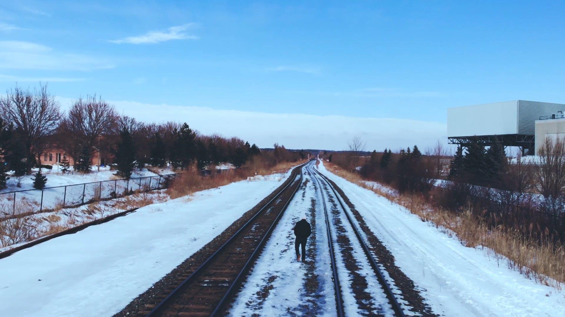 Photo of Man Walking On Railroad During Winter