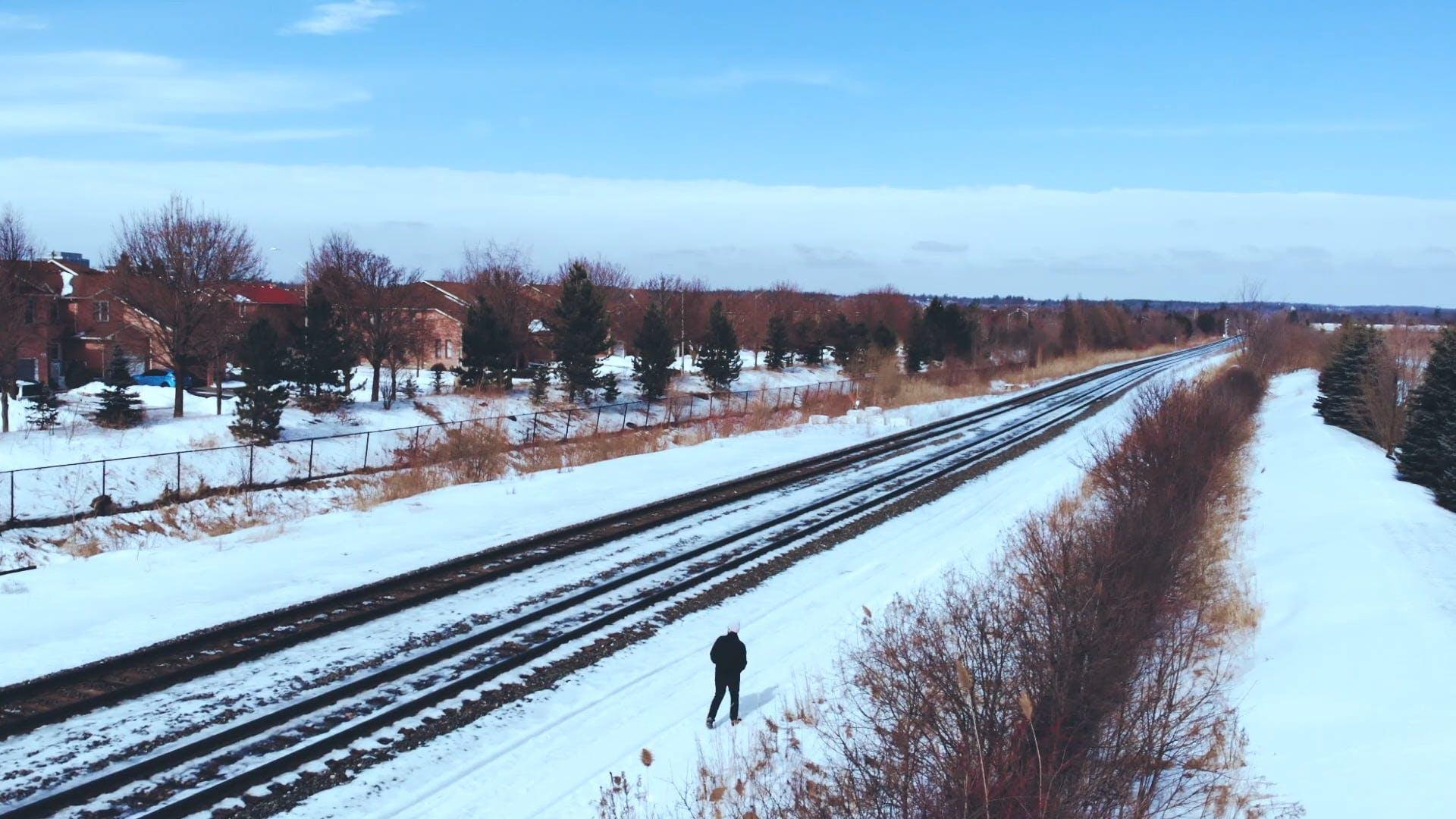 Man Walking Beside Railroad In Winter