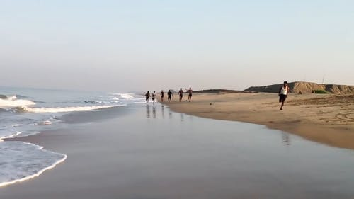 People Running Along The Shore