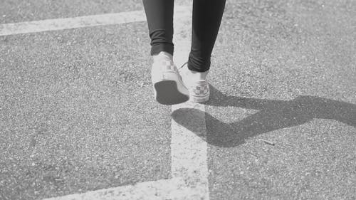 Person Walking And Following The Painted Lines In The Ground