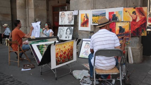 People Painting and Sketching Outside A Building
