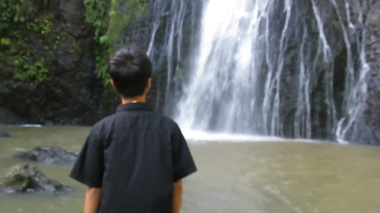 A Boy Watching A Waterfalls