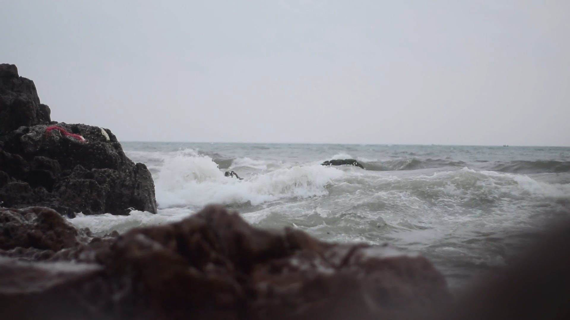 Close-Up View Of Waves Crashing To The Rocks