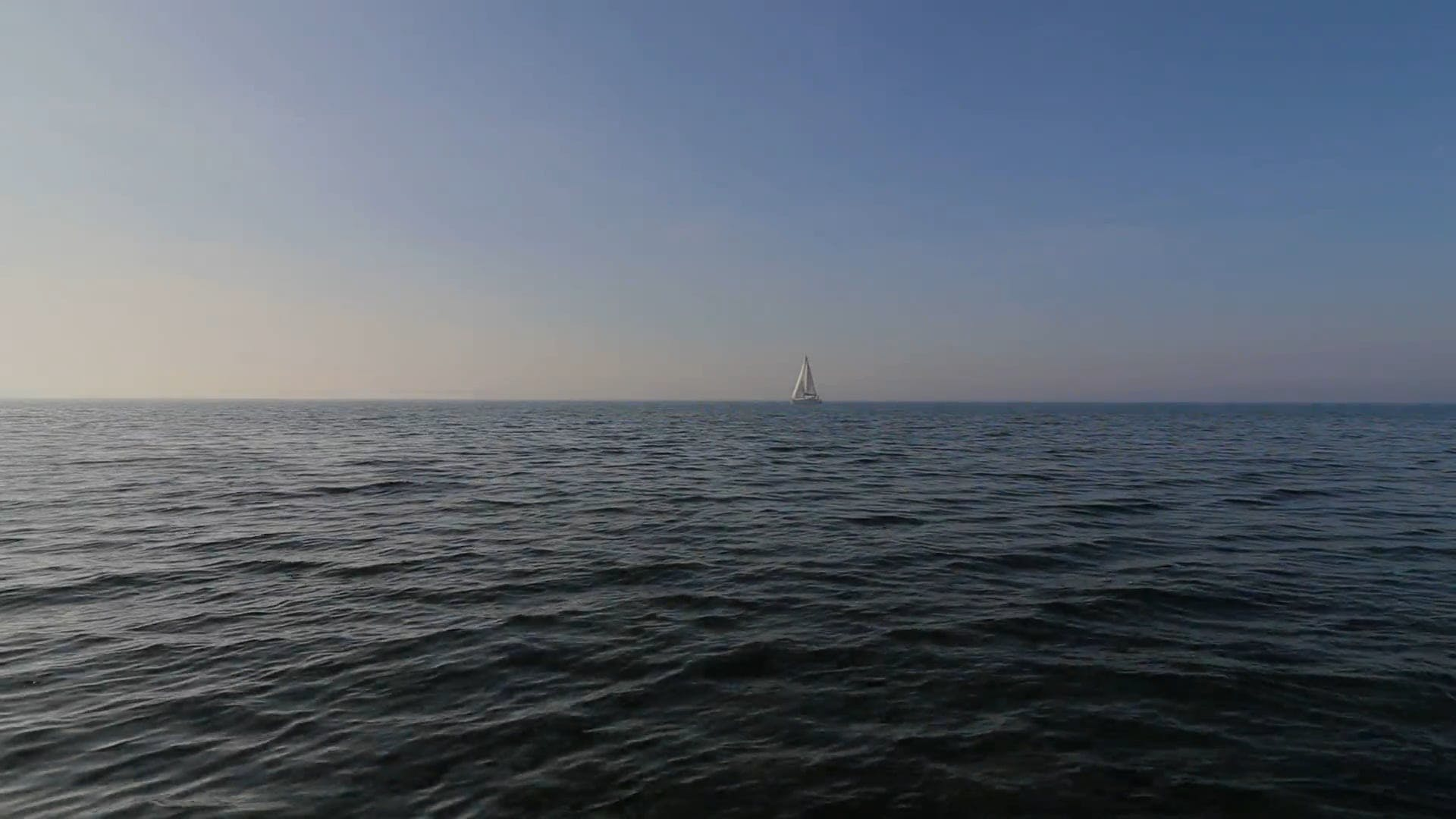 A Boat Sailing In The Middle Of The Sea