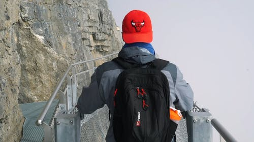 Man Crossing A Bridge On The Side Of A Mountain