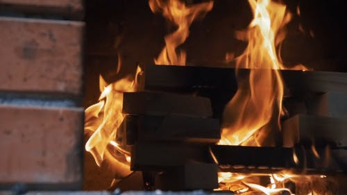 Close-Up Of Wood Burning Into Flames In The Fireplace In Slow Motion
