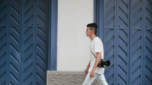 Man Walking Along The Sidewalk Carrying A Camera