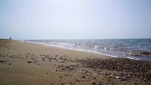 Waves Lapping On A Sandy Shore At Daytime