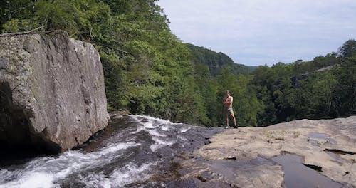 Man Standing On A Cliff Near Waterfalls