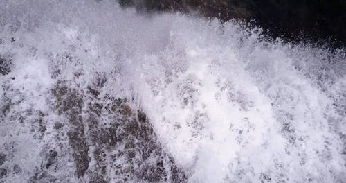 Aerial Footage Of Water Rapidly Flowing Down A Fall To A Rocky River Bed