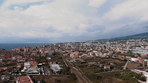 Aerial Footage Of A City Along The Coastline In Daylight