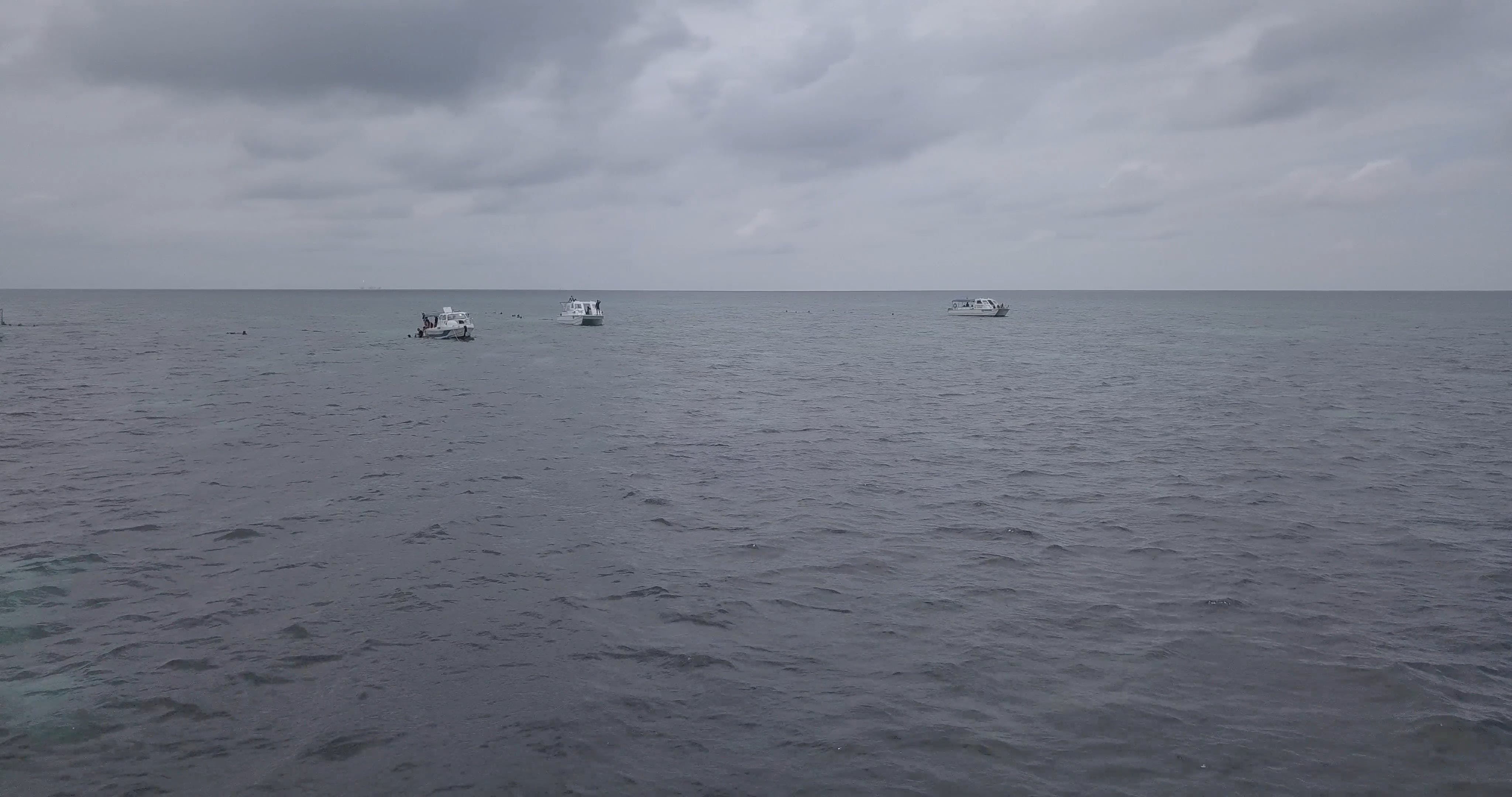 People In Boats And Swimming In The Sea