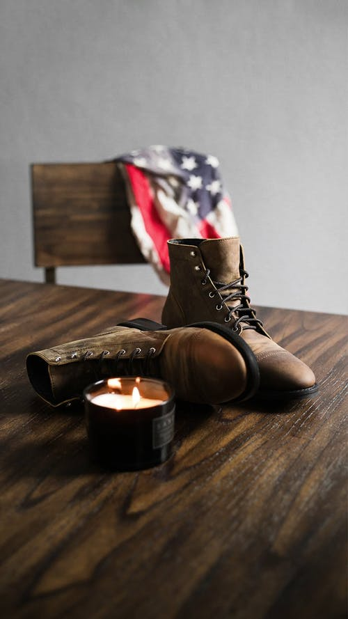 Lighted Candle And Boots On Table