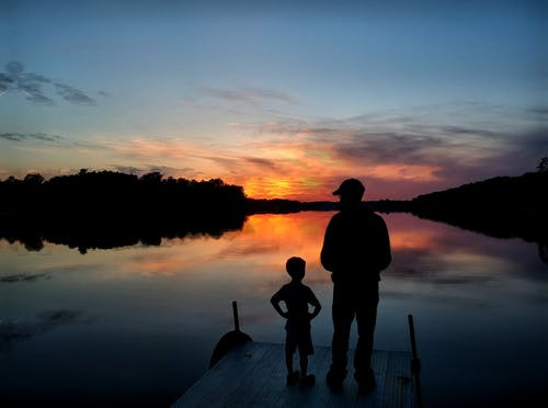 Man And Kid Looking At Sunset