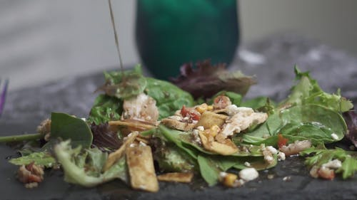Pouring dressing On Green Salad