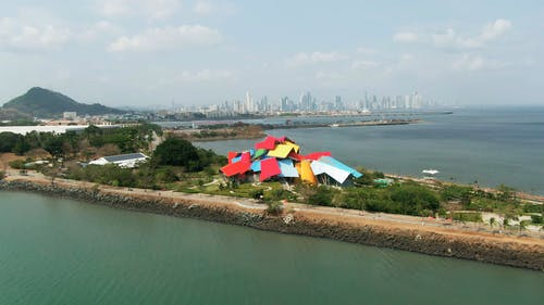 Aerial Footage Of Building With Distinct Architectural Design In  A Coastal City And Its Surrounding Landscape