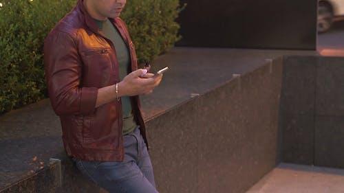 Man Vaping While Using His Phone