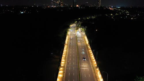 Aerial Footage Of Well Lighted City Streets Traffic And Surrounding Landscape