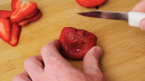 Person Slicing Fresh Strawberries On A Chopping Board