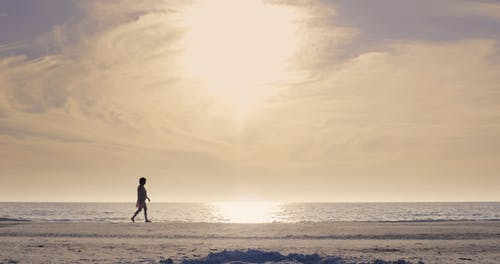 Low Angle Footage Of A Woman Walking Along The Beach
