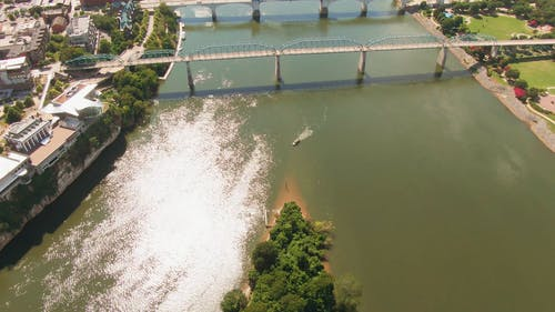 Aerial Footage Of Bridges Across A River In A City With The View Of The Mountains