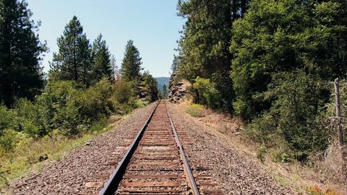 A Railroad Track Cuts Through The Rocky Mountain Side