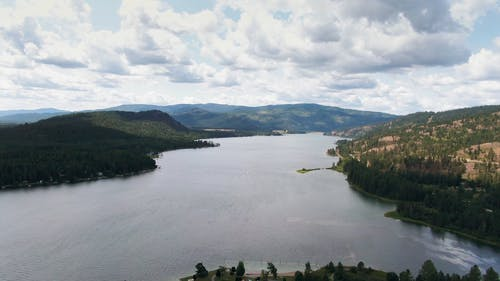 Aerial Footage Of A Lake Surrounded By Hills And Mountains