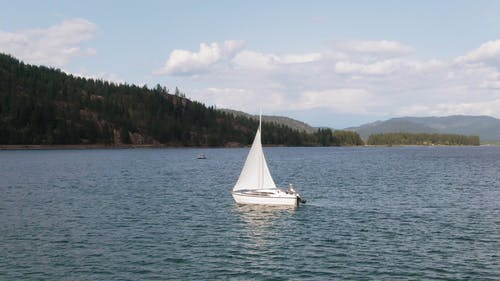 A Sailboat Floating In The Middle Of A Lake