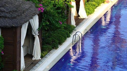 Frau, Die In Einem Mit Cabanas Ausgekleideten Pool Schwimmt
