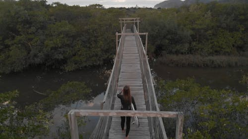 Slow Motion Footage Of A Woman  Carrying A Surfboard Crossing A Wooden Bridge leading Into The Woods
