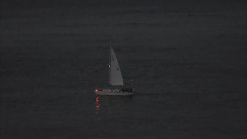 A Sailboat Sailing At Night