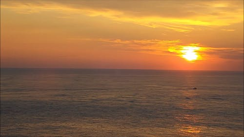 Sun Setting And The Moon Rising In The Horizon Above The Sea