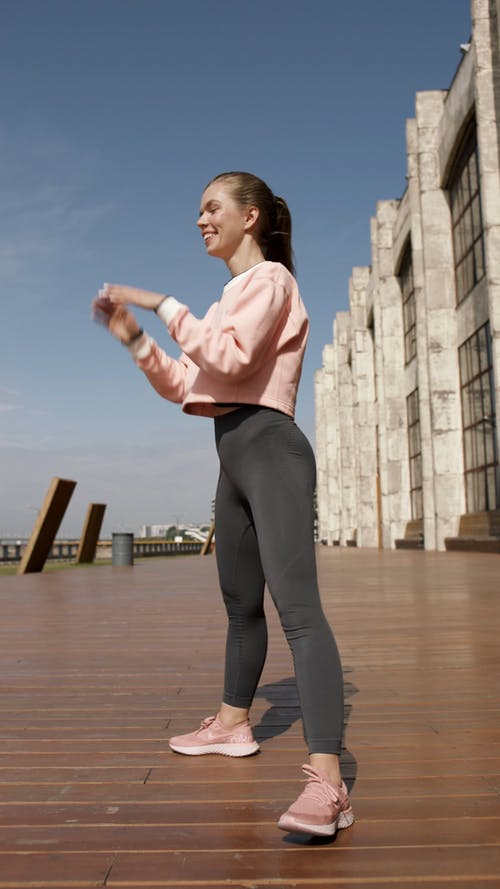 Woman In Pink And Gray Sports Gear Exercising Outdoors