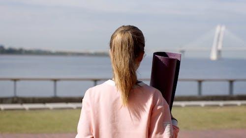 Woman With Yoga Mat Walking Near A Seaport