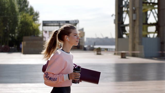 Woman Walking By The Seaport Holding A Yoga Mat And Drinking Water