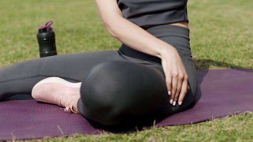 A Woman With Good Flexibility Stretching Outdoors On Grassy Lawn