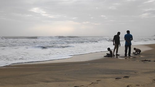 Kids Playing On Sandy Beach Close To Two Male Adults In Conversation While Standing