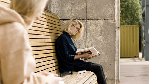 A Woman Seated On A Bench With Her Books
