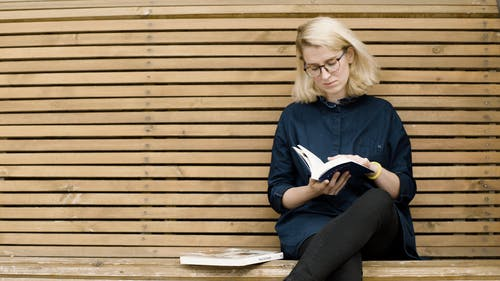 Woman Reading A Book While Waiting