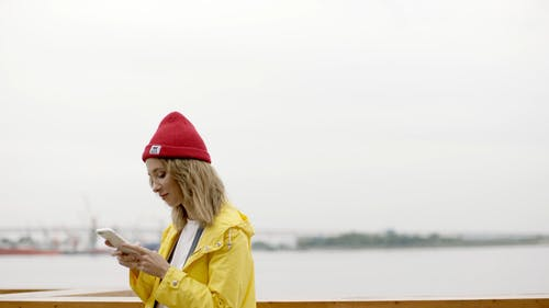 Woman Using Her Smartphone Standing Near Body Of Water