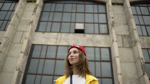 Woman In Red Beanie And Yellow Jacket In Front Of A Building