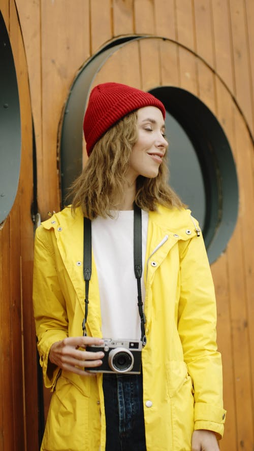 Woman In Red Beanie And Yellow Jacket With Camera